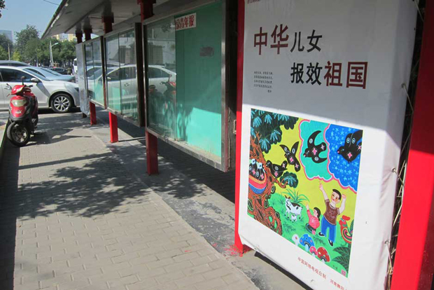 """Chinese boy and girls, serve the country"": This mild patriotic message is further softened by a peasant painting of children at play."